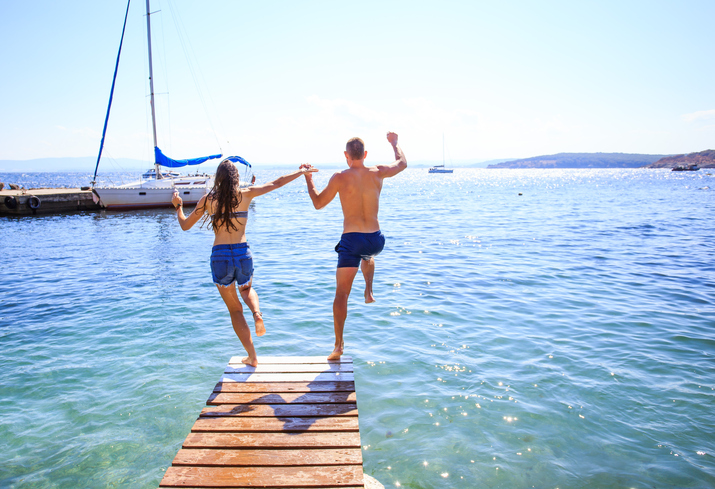 couple jumping into the ocean - temecula pain management clinic